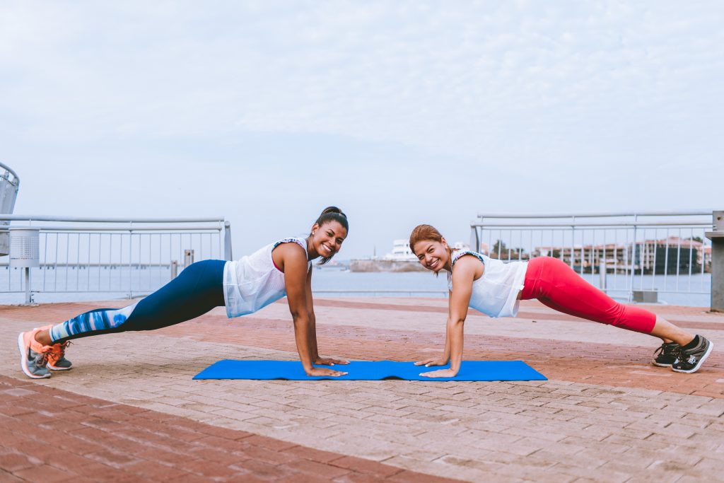 Two women doing a plank exercise outside on www.healthynexercise.com image