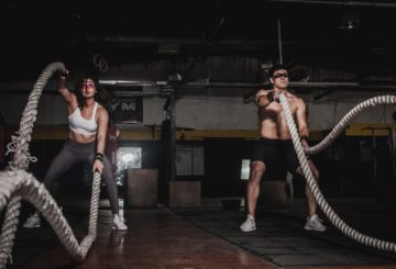 Woman & Man working out with battle ropes